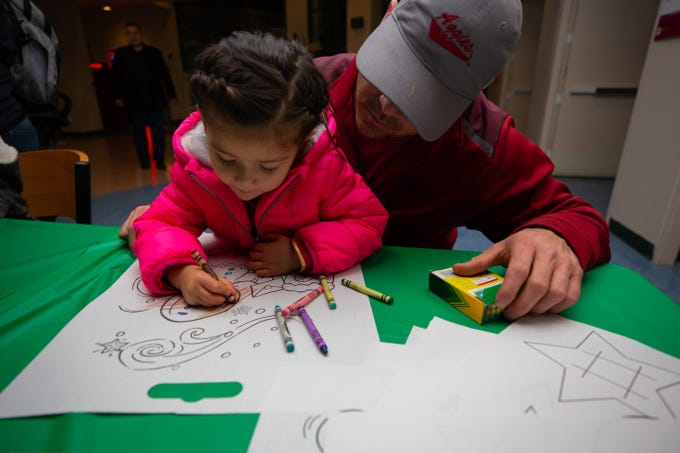 Avery Aranda, 3, with her father Mark watching, colors a snowman during the Noche de Luminarias event coloring workshop held on Sunday, Dec. 2, 2018, at New Mexico State University.