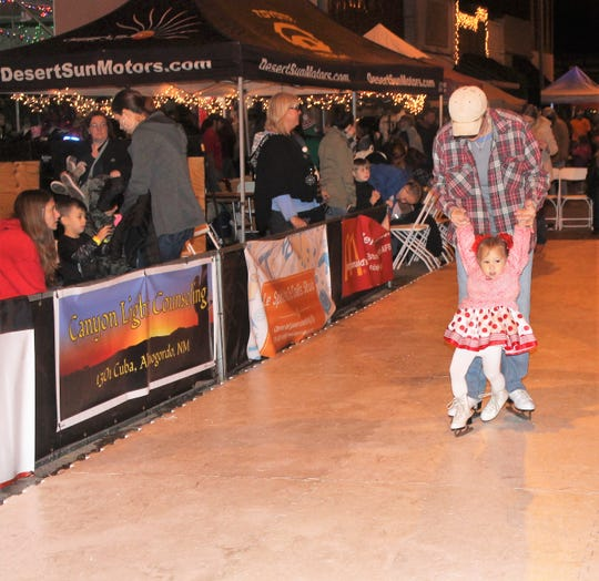 Alexa Archuleta and Jen Byrnes skate on the artificial skating rink at Olde Fashioned Christmas Saturday.  The artificial ice skating rink was sponsored by Desert Sun Auto Group.