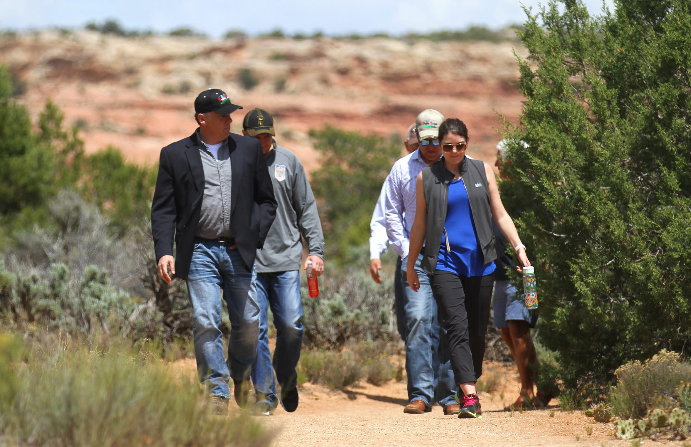 San Juan County, Utah, Commissioner Phil Lyman, left, makes his way to a press conference,  Monday,May 8, 2017 at Butler Wash southwest of Blanding, Utah.
