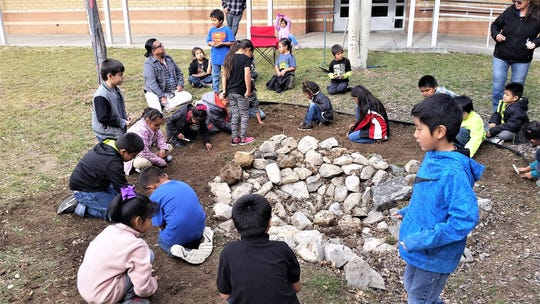 First grade students begin the planting process of the spring bulbs after the dirt has been tilled by the high school students