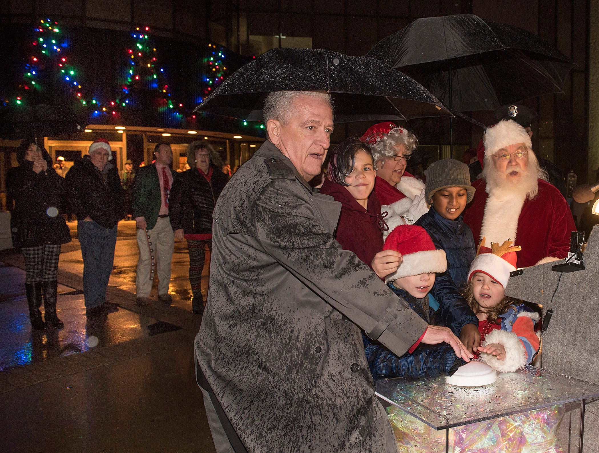 """Mayor Dennis Wright, Santa and Mrs. Claus light the holiday lights with help from winners of the """"December is Special To Me"""" contest, Steven Saylor, Michael Mastaw, Sriyansh Priyadarshi, and Evelyn Talbot."""