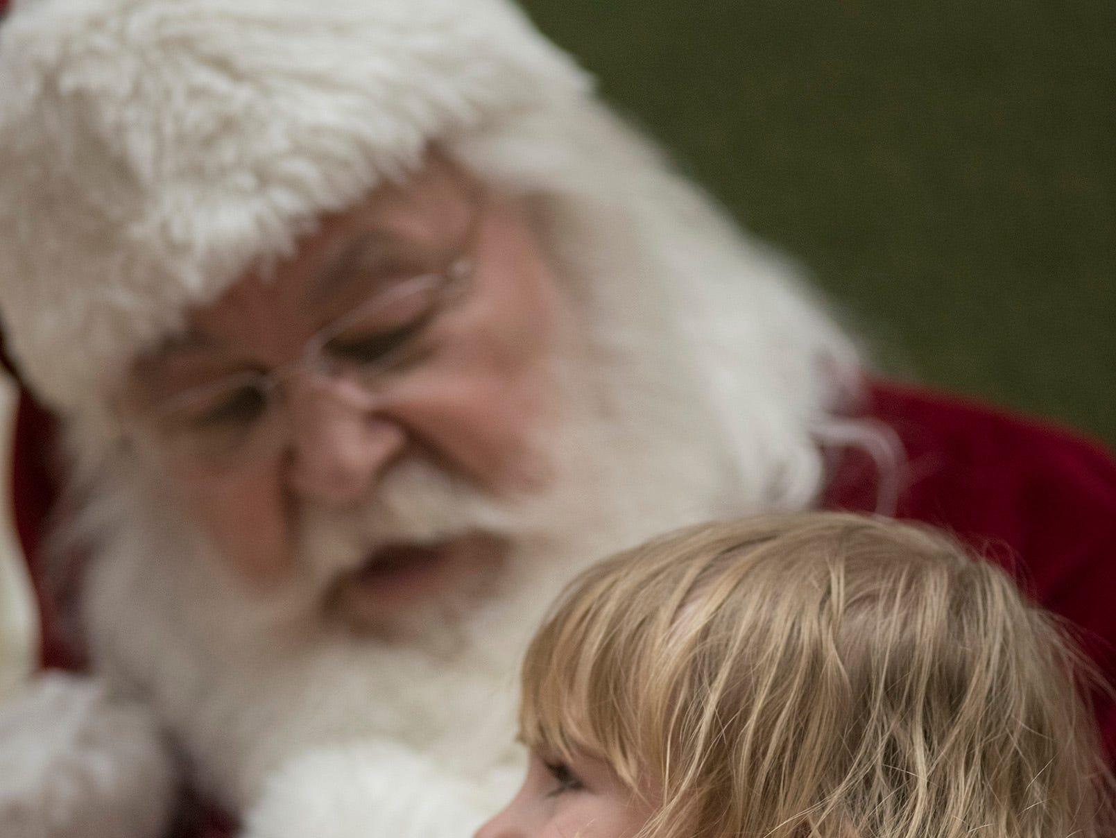 Three year old Glenn Mitchell greets Santa.