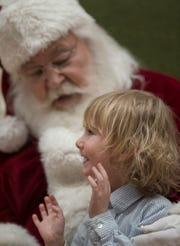 Three year old Glenn Mitchell greets Santa.