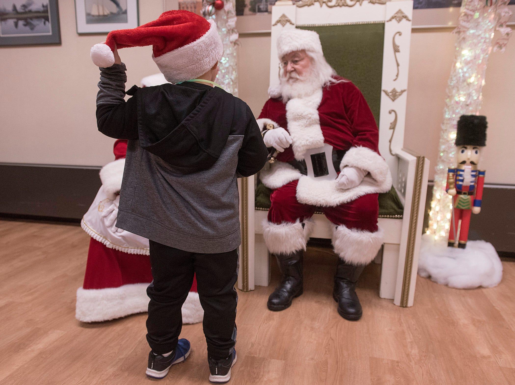Five year old Benjamin Kerkhof shows off his Santa hat to the man himself.