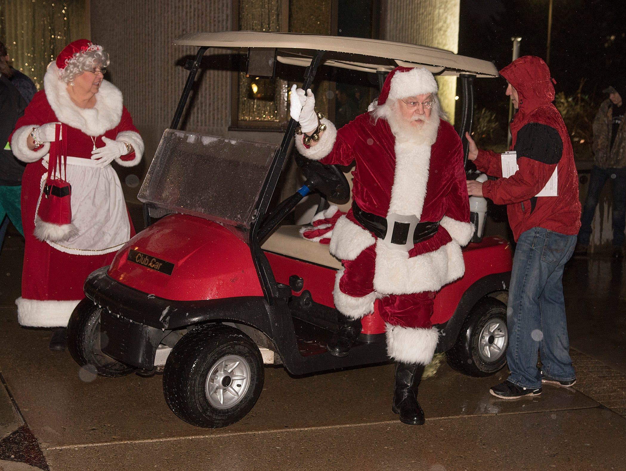 Santa and Mrs. Claus make their final approach in a Santa Claus red golf cart.
