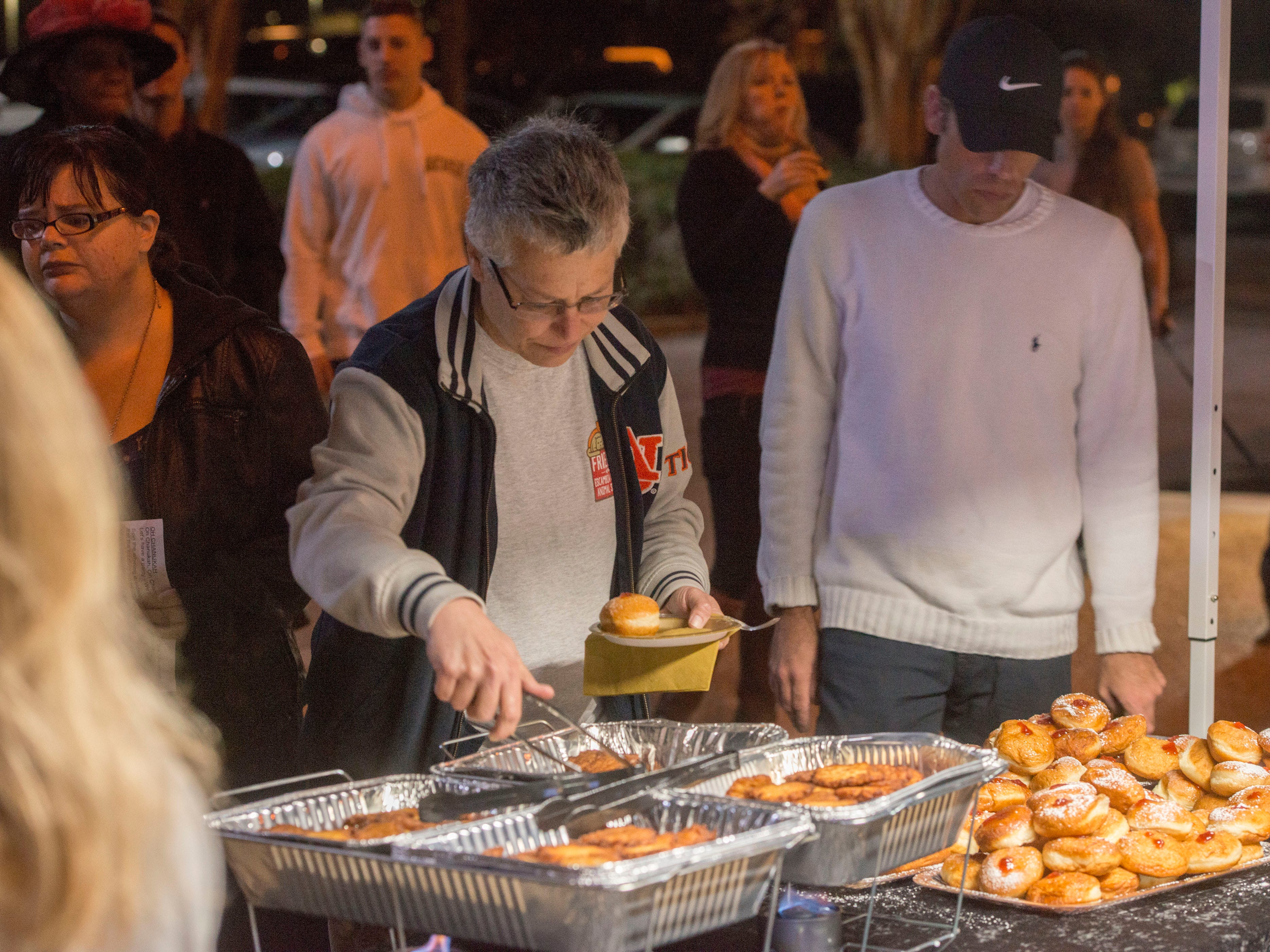 Visitors help themselves to snacks Sunday, December 2, 2018 during the Chabad of Pensacola Grand Menorah Lighting at Pensacola City Hall.