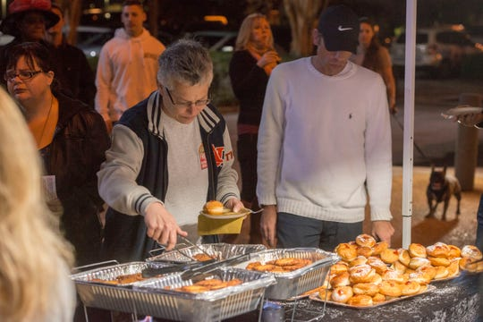 Visitors help themselves to snacks Sunday at the Pensacola Chabad Jewish Center's Grand Menorah Lighting at Pensacola City Hall.