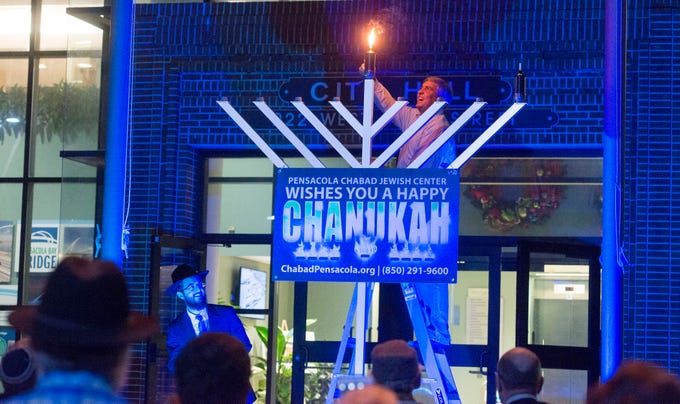 Pensacola Mayor Grover Robinson lights the first candle Sunday, December 2, 2018 during the Chabad of Pensacola Grand Menorah Lighting at Pensacola City Hall.