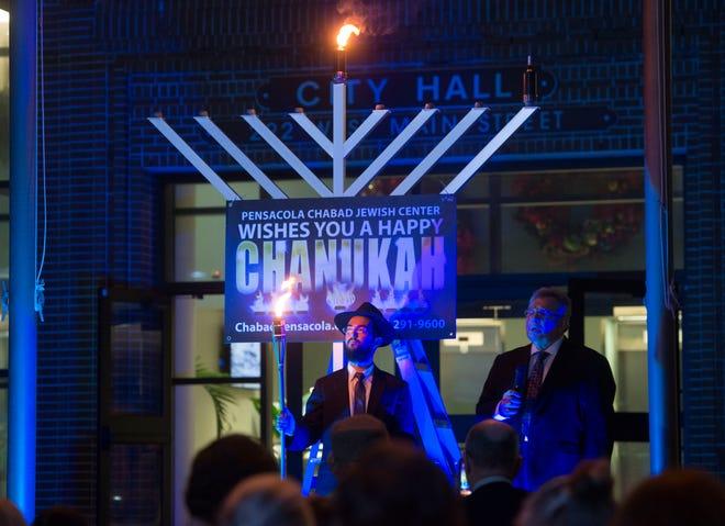 RabbiMendel Danow and Rabbi Sam Waidenbaum sing with the crowd Sunday during the Pensacola Chabad Jewish Center's Grand Menorah Lighting at Pensacola City Hall to mark the start of Hanukkah.
