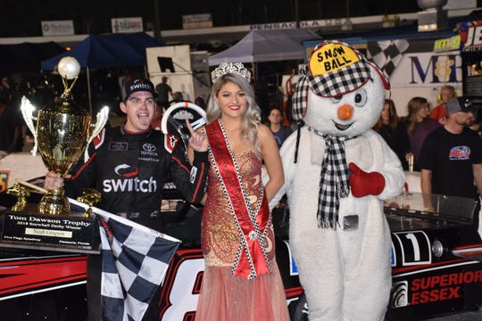 Noah Gragson holds checkered flag and Tom Dawson trophy, joined by Miss Snowball Derby Helena Ciappina, a Tate High grad and Pensacola State College student, along with Snowball mascot after winning 51st Snowball Derby at Five Flags Speedway