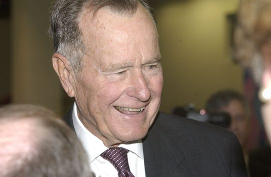 Former President George H.W. Bush makes his way through a receiving line Jan. 9, 2004, at the National Naval Aviation Museum in Pensacola. Bush was the honorary chairman of the museum's foundation and was saluted at a dinner for his support of the museum.