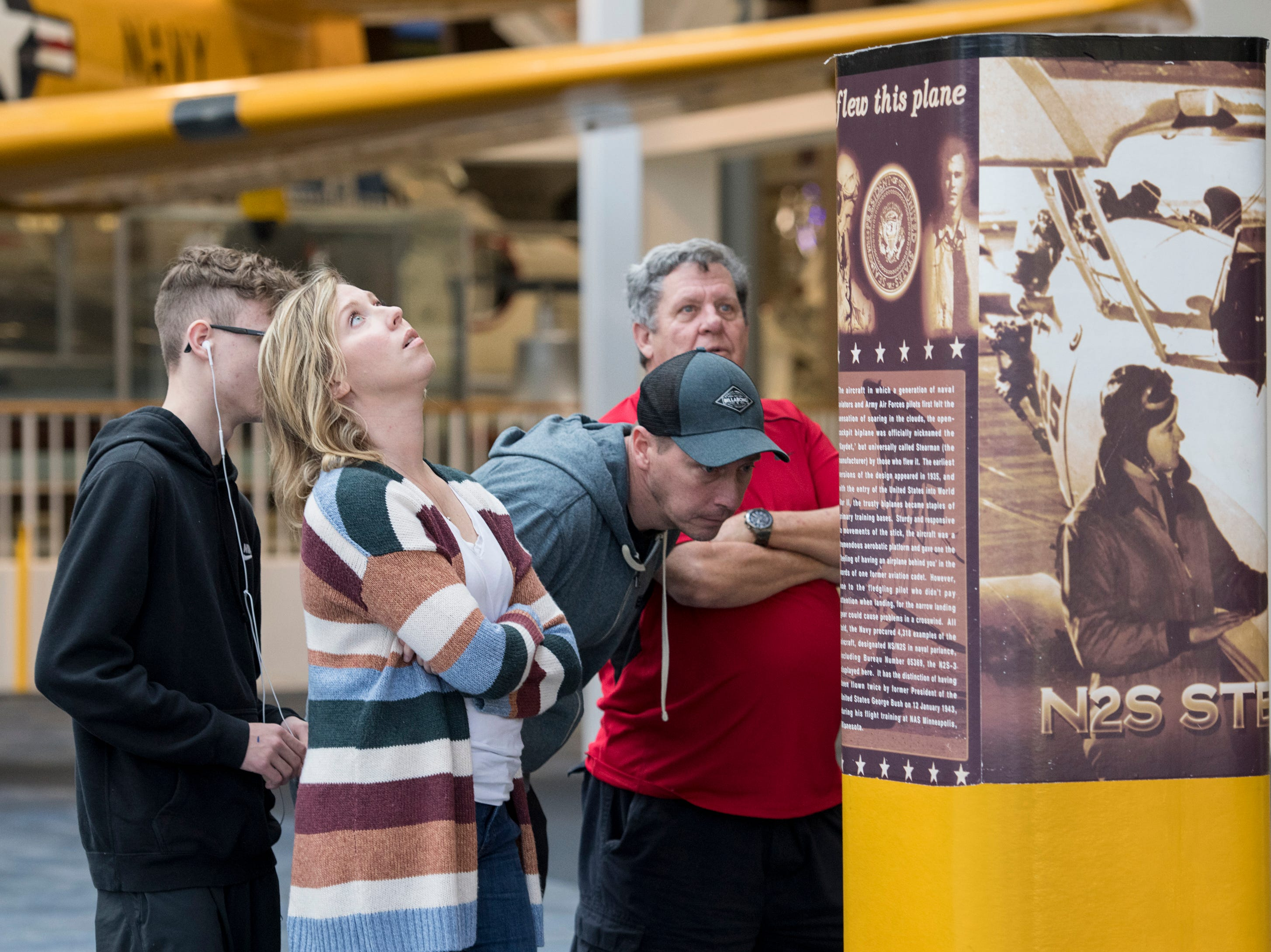 Colin Nance, 14, from left, Charity Nance, and Bryan Nance, of Navarre, along with Mickey Cochran, of Columbus, Ohio, check out the Stearman biplane flown by President (then cadet) George H.W. Bush while training during World War II on display at the National Naval Aviation Museum in Pensacola on Monday, December 3, 2018.
