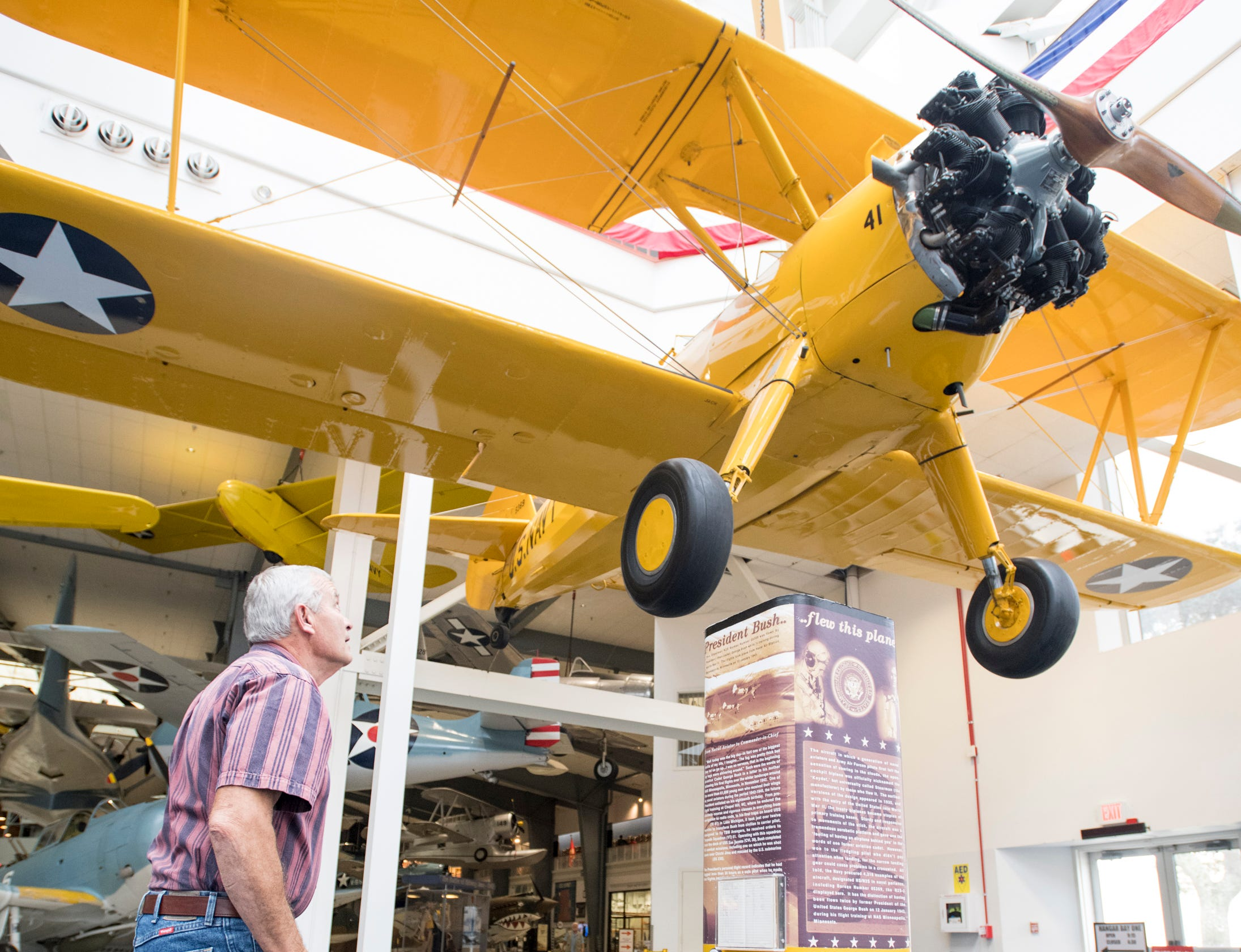 Joe Bright, of Knoxville, Tennessee, looks up at the Stearman biplane flown by President (then cadet) George H.W. Bush while training during World War II on display at the National Naval Aviation Museum in Pensacola on Monday, December 3, 2018.