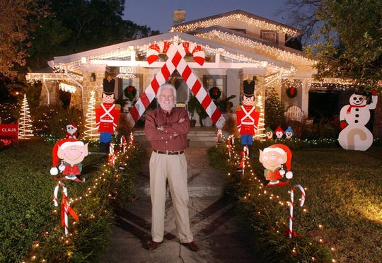 Mike Burleson stands in front of the winter wonderland he creates each year in his yard at 17th Avenue and Gadsden Street in East Hill in this file photo from December 2003.