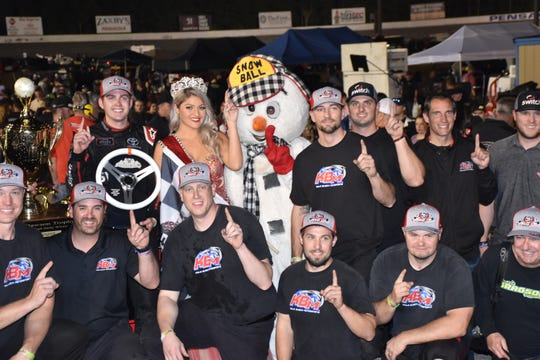 Noah Gragson, holding steering wheel trophy, along with Miss Snowball Derby Helena Ciappina, are joined by members of Gragson's team from Kyle Busch Motorsports in Victory Lane after winning the 51st Snowball Derby Dec 2 at Five Flags Speedway