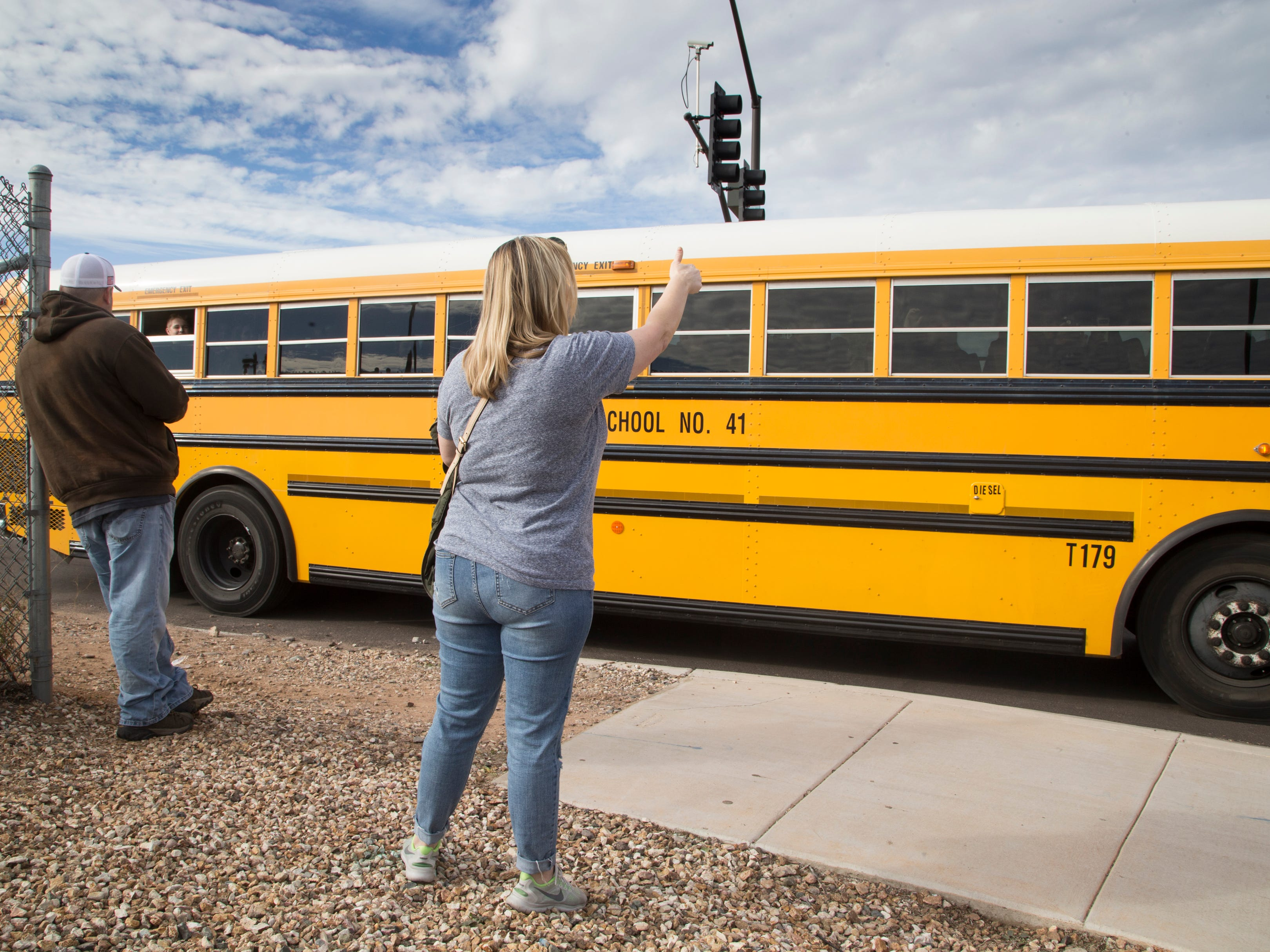 "Shannon Kelly gestures to her goddaughter Dec. 3, 2018, at Highland High School. Students were being bused to Highland Junior High School after an ""unsubstantiated"" bomb threat put Highland High on lockdown."