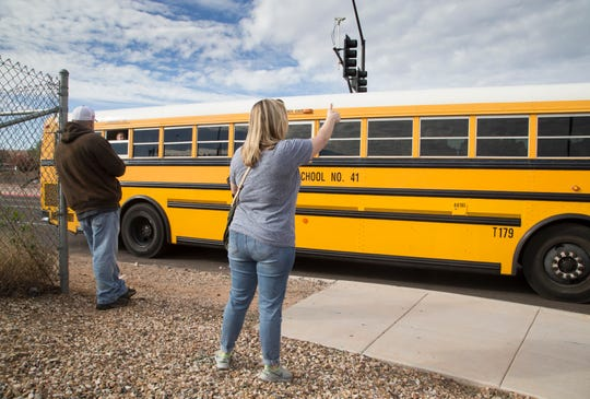 """Shannon Kelly gestures to her goddaughter Dec. 3, 2018, at Highland High School. Students were being bused to Highland Junior High School after an """"unsubstantiated"""" bomb threat put Highland High on lockdown."""
