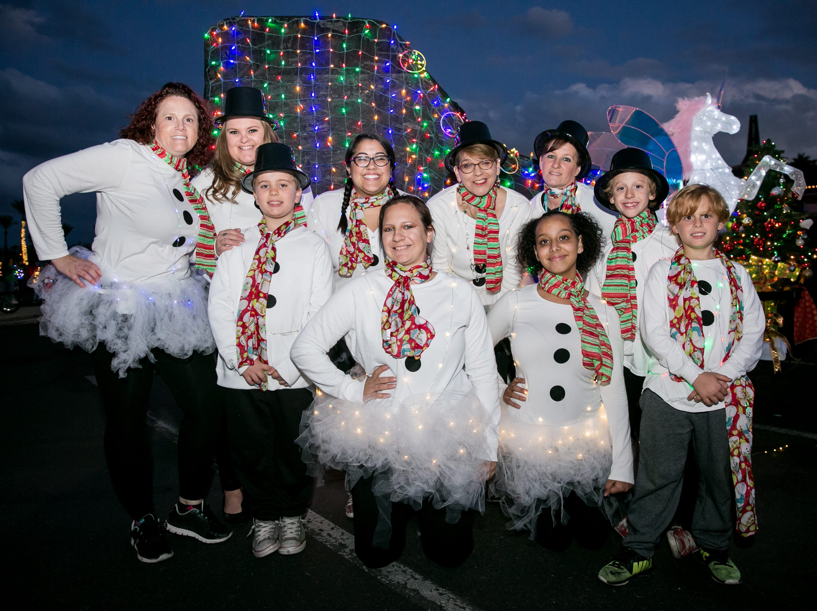 The Desert Dolls Roller Derby crew posed in front of a lit up skate during the APS Electric Light Parade in Central Phoenix on Saturday, December 1, 2018.