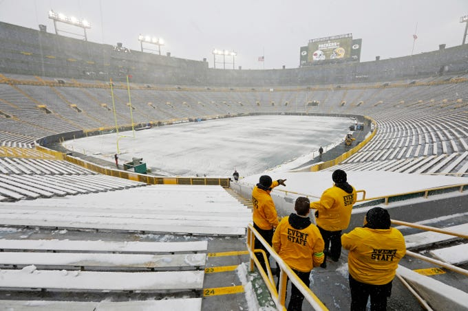 Event staff look out at a snow covered Lambeau Field before the game between the Green Bay Packers and the Arizona Cardinals on Sunday, Dec. 2, 2018, in Green Bay, Wis.