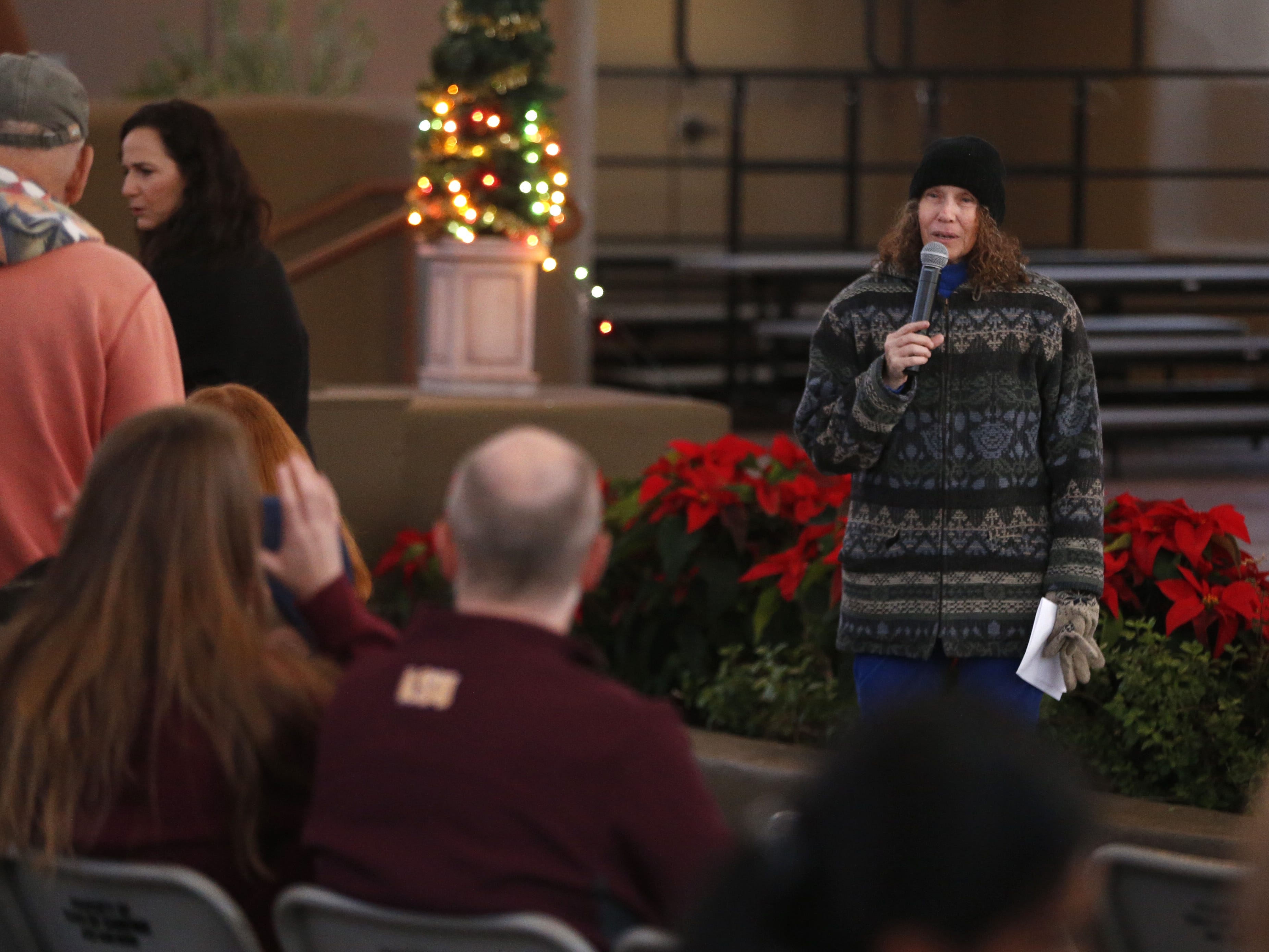 Ora Kurland, founder of Jewish Social Group of Cave Creek and Carefree, asks the people to join her on stage around the menorah during a Menorah Lighting Ceremony on the first night of Hanukkah at Carefree Desert Gardens in Carefree, Ariz. on December 2, 2018.