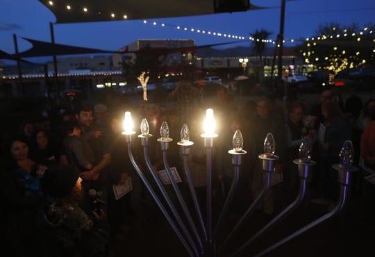 The menorah lights up during a Menorah Lighting Ceremony on the first night of Hanukkah at Carefree Desert Gardens in Carefree, Ariz. on December 2, 2018.