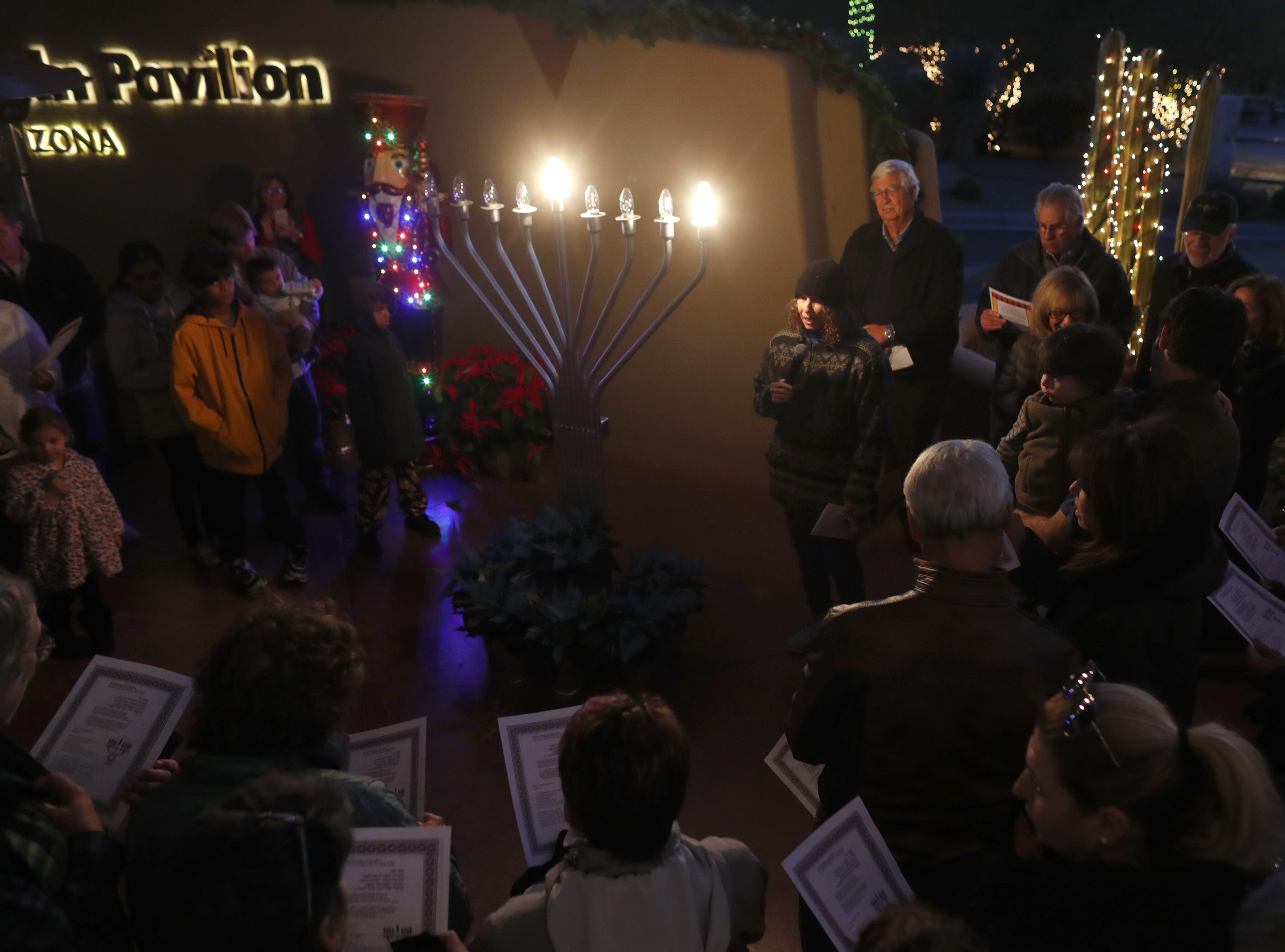 Ora Kurland leads people in song during a Menorah Lighting Ceremony on the first night of Hanukkah at Carefree Desert Gardens in Carefree, Ariz. on December 2, 2018.
