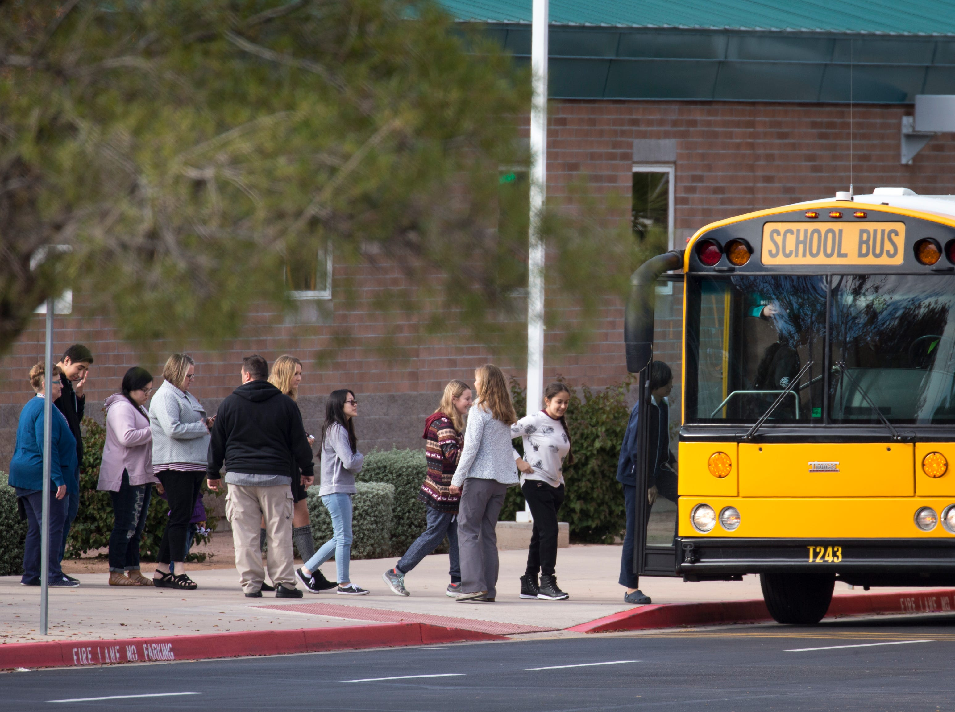 "Highland High School students are loaded into a bus Dec. 3, 2018, at Highland High School in Gilbert.  The students were being bused to Highland Junior High School in Gilbert after an ""unsubstantiated"" bomb threat put Highland High on lockdown."