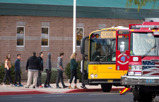 """Highland High School students are loaded into a bus Dec. 3, 2018, at Highland High School in Gilbert.  The students were being bused to Highland Junior High School in Gilbert after an """"unsubstantiated"""" bomb threat put Highland High on lockdown."""