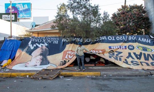 Migrantes permanecen hoy a la intemperie fuera del albergue original que resultó inhabitable luego de las fuertes lluvias en Tijuana (México).
