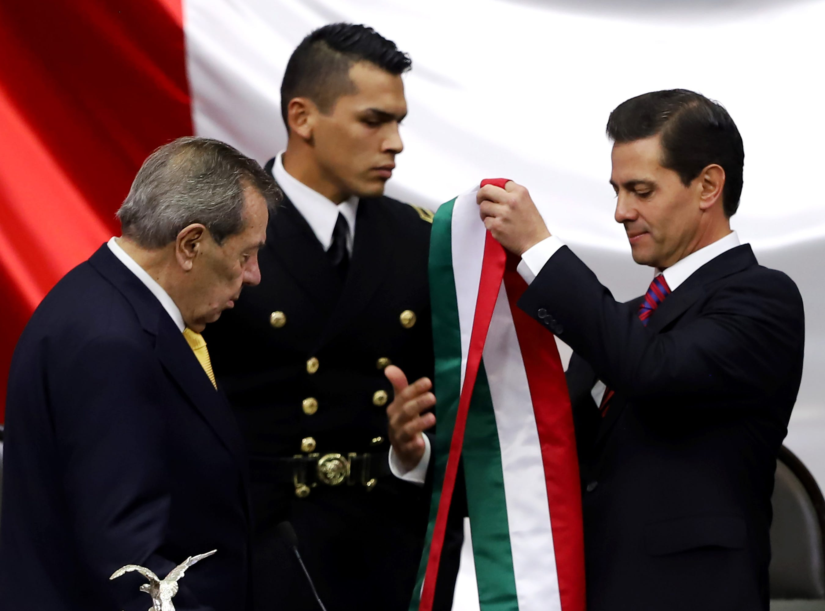 MEXICO CITY, MEXICO - DECEMBER 01: Outgoing Mexican President Enrique Peña Nieto (R) hands over the presidential sash to President of the Chamber of Deputies Porfirio Munoz Ledo (L) during the events of the Presidential Investiture as part of the 65th Mexico Presidential Inauguration at Congress of the Union on December 01, 2018 in Mexico City, Mexico. (Photo by Getty Images/Getty Images)