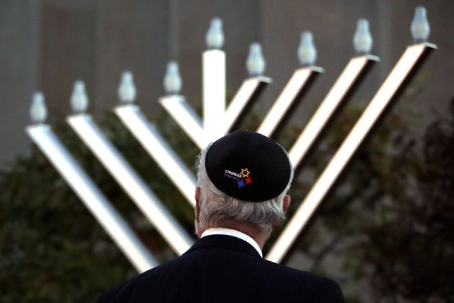 Rabbi Jeffrey Myers watches the installation of a menorah outside the Tree of Life Synagogue before holding a celebration on the first night of Hanukkah, Sunday, Dec. 2, 2018, in the Squirrel Hill neighborhood of Pittsburgh. A gunman shot and killed 11 people while they worshipped Saturday, Oct. 27, at the temple. (AP Photo/Gene J. Puskar)