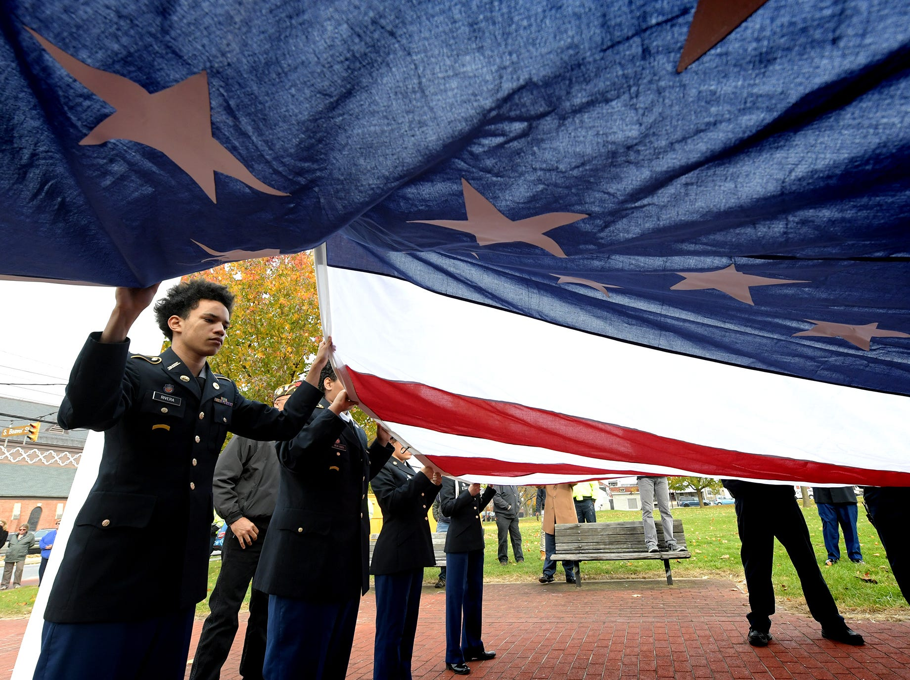 York High School Junior ROTC member Sheldrek Rivera drapes the the Penn Park flag with other members during a flag raising ceremony at the park Monday, Nov. 12, 2018. State Representative Carol Hill-Evans' office secured the purchase of the 20'x30' American flag and the City of York provided upgrades to the flagpole and lighting. The York County Department of Veterans Affairs will be in charge of flag replacement as needed. The flagpole at Penn Park has been vacant since 2012. Bill Kalina photo