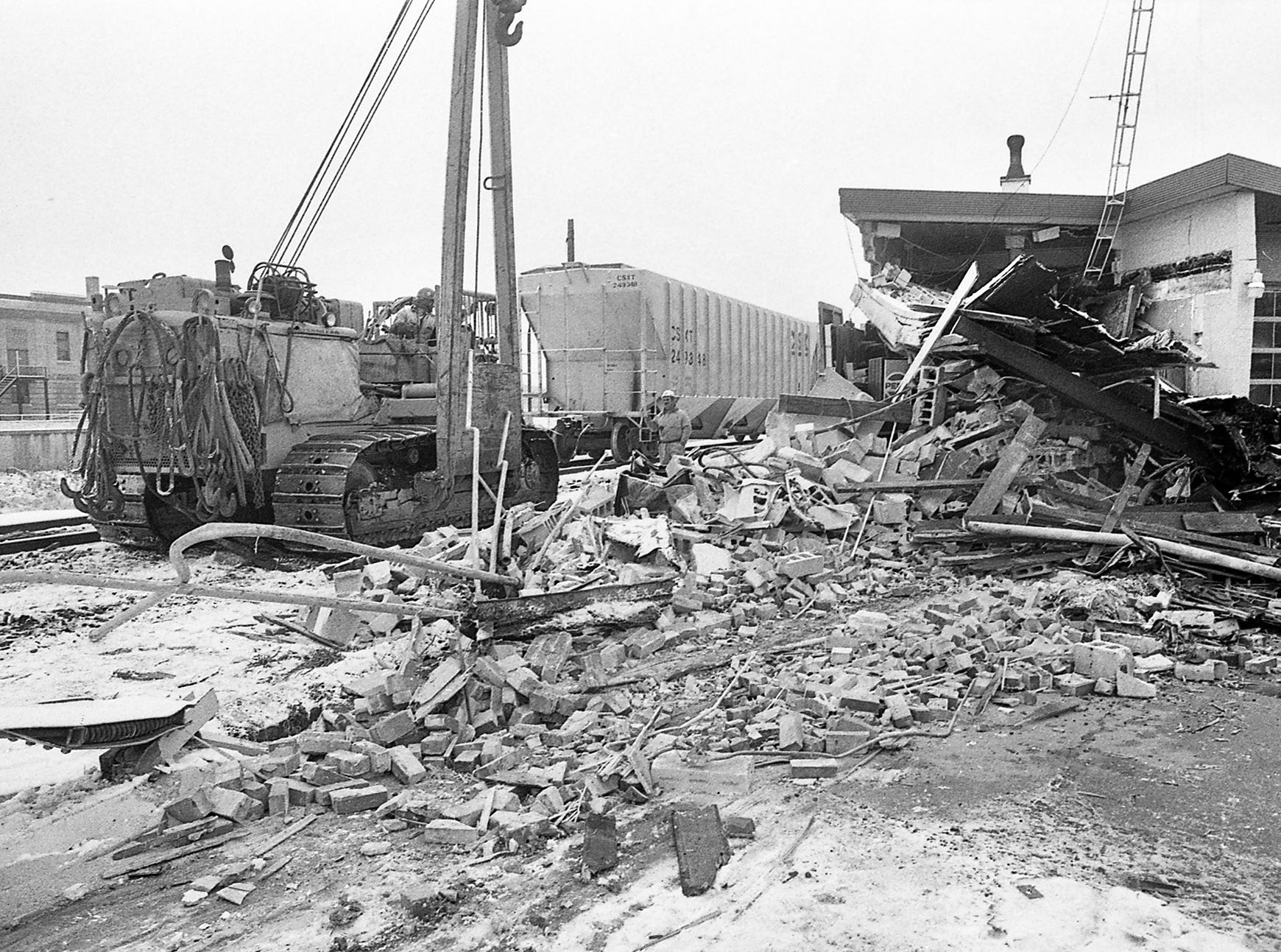 In December 1989, a train left the tracks near Arch Street and North George Street in York and destroyed Ellis Brothers. Heavy equipment is used to clean up the incident. In the background at left is the armory that still stands today.