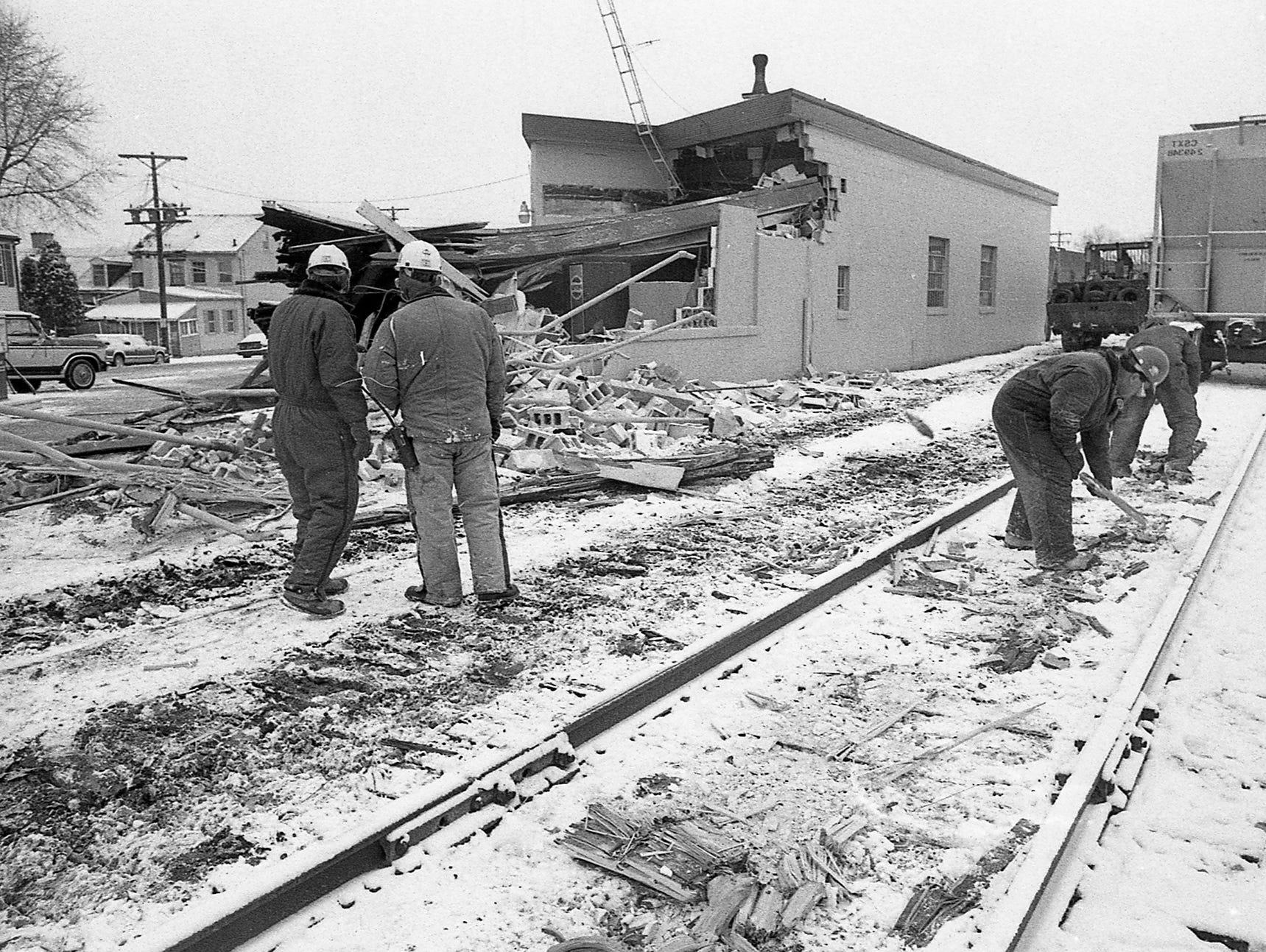 In December 1989, a train left the tracks near Arch Street and North George Street in York and destroyed Ellis Brothers. Workers inspect the track after the incident.