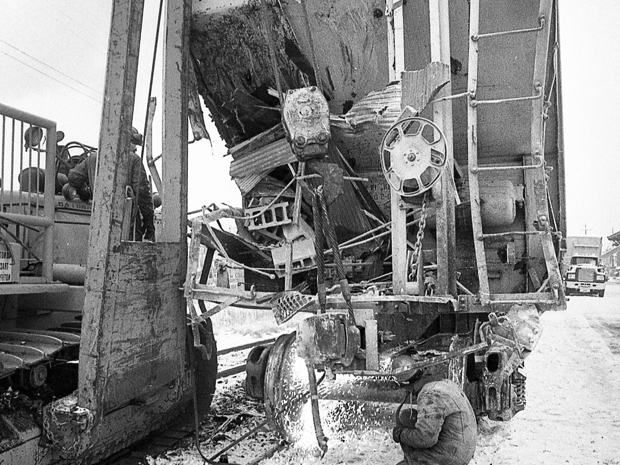 A torch is used to work on a damaged freight car after it collided with Ellis Brothers. In December 1989, a train left the tracks near Arch Street and North George Street in York and destroyed Ellis Brothers.
