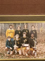 Olympia cross country coach Bob Goodell, in the yellow shirt, with the 1975 team that qualified for the state meet.