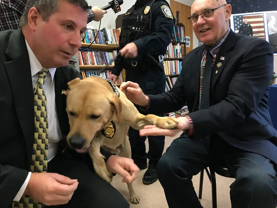 Sonny, the Gates Police Department's drug dog, is sniffing for a treat from Gates Town Supervisor Cosmo Giunta, left, while high-fiving Monroe County Legislator Frank Allkofer, who represents Gates.