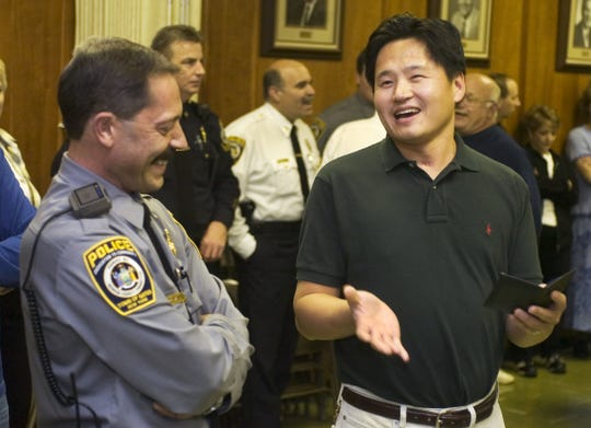 "Sung ""Sonny"" Chung, right, laughs with Gates Constable Mario Madau after accepting his retirement badge and service plaque in 2004."