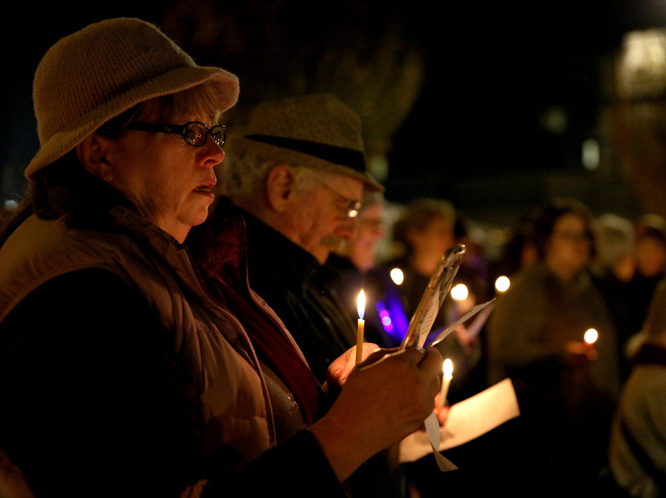 Attendees of a menorah lighting, hosted by the Chabad Center for Jewish Life, sing songs on the first day of Hanukkah at Mirror Park in downtown Salem on Sunday, Dec. 2, 2018. The candles were lit to show solidarity with the Jewish community in Pittsburgh.
