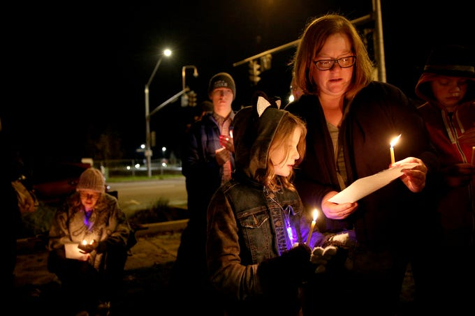 Menorah lighting attendees Autumn Hofer and her 8-year-old daughter Addie Hofer read the lyrics to a song during a celebration on the first day of Hanukkah at Mirror Park in downtown Salem on Sunday, Dec. 2, 2018.