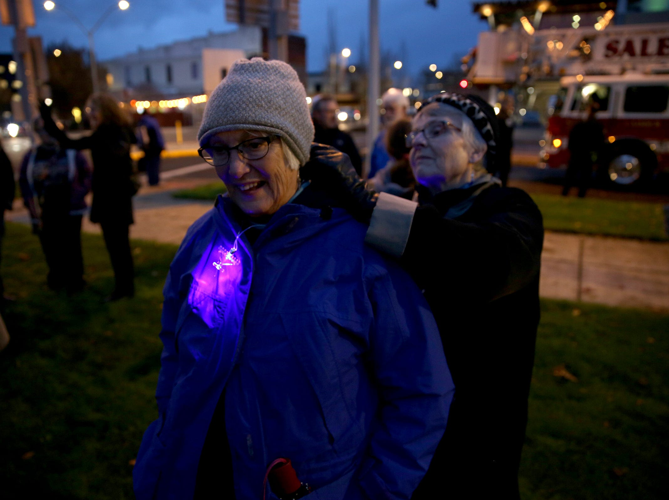 Mary Gabriel helps Yael Ben-Ari put on a light-up menorah necklace during a celebration on the first day of Hanukkah at Mirror Park in downtown Salem on Sunday, Dec. 2, 2018.