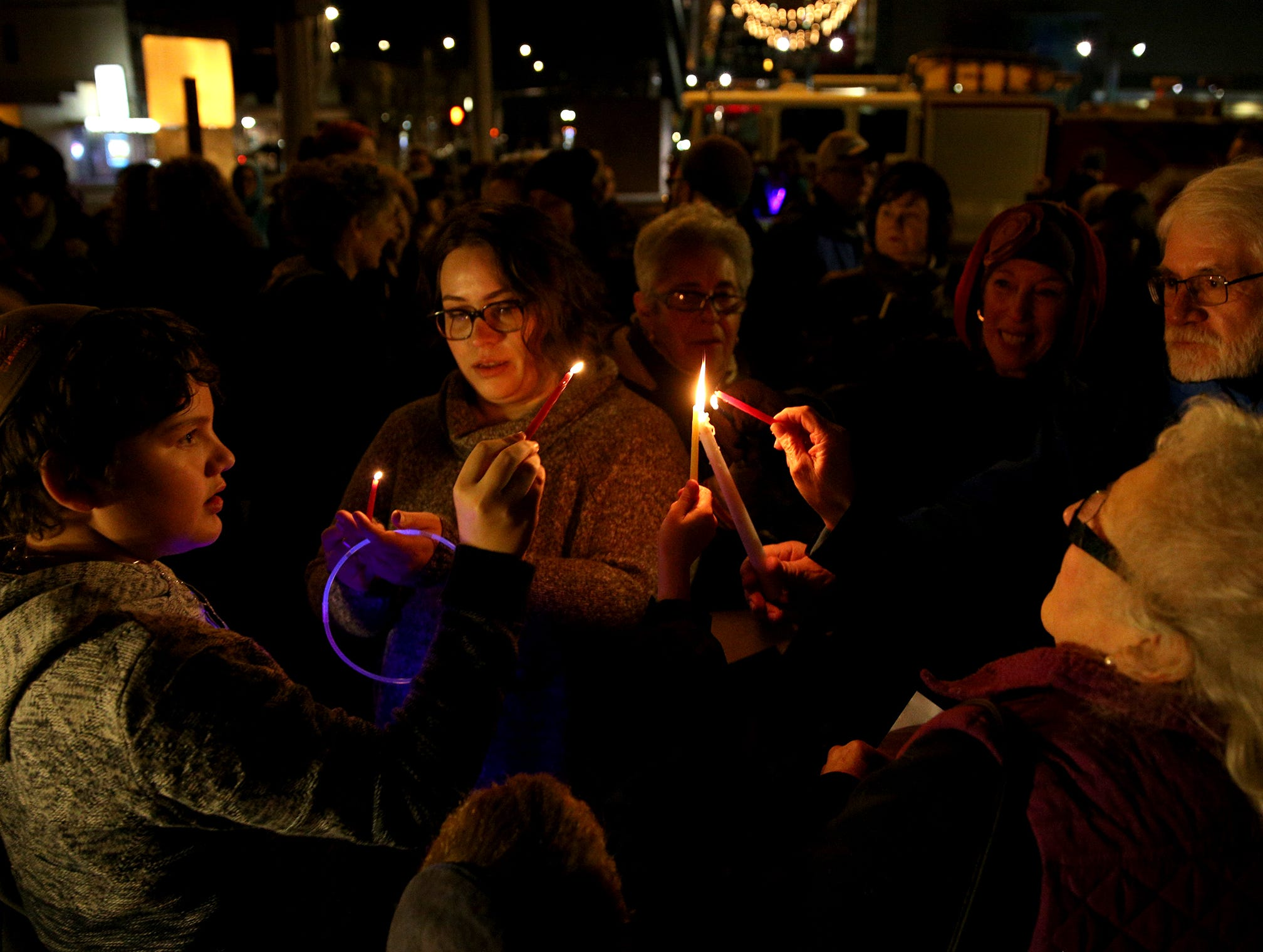 Attendees of a menorah lighting, hosted by the Chabad Center for Jewish Life, light candles on the first day of Hanukkah at Mirror Park in downtown Salem on Sunday, Dec. 2, 2018. The candles were lit to show solidarity with the Jewish community in Pittsburgh.