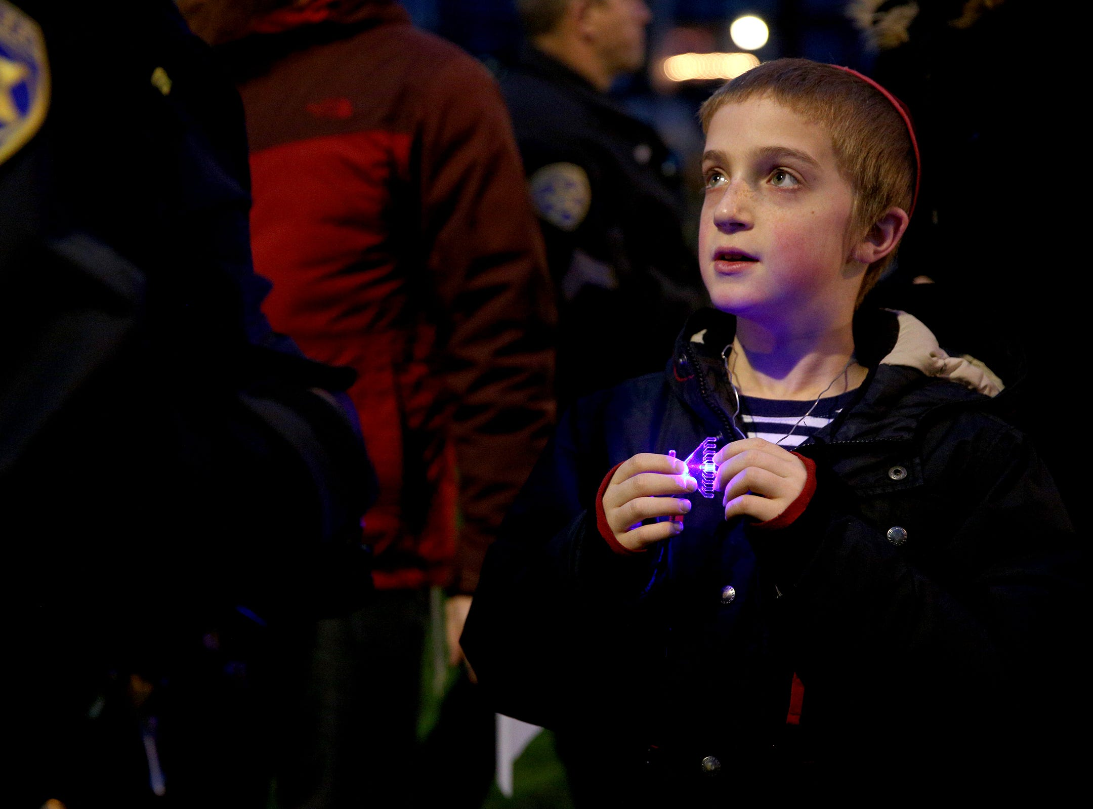 Sholom Perlstein, 10, holds a light up menorah necklace during a celebration on the first day of Hanukkah at Mirror Park in downtown Salem on Sunday, Dec. 2, 2018.