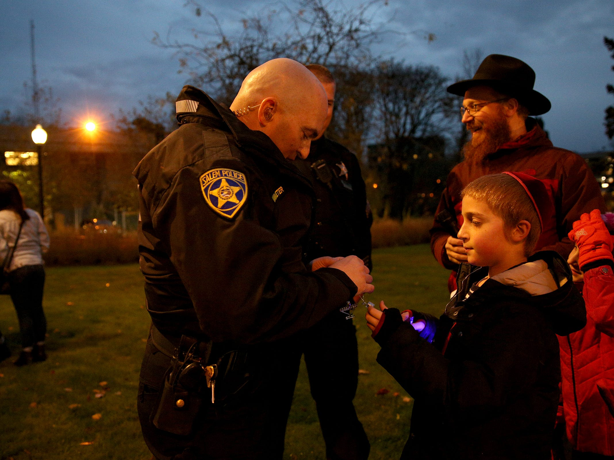 Sholom Perlstein, 10, offers a necklace to Salem Police department Sergeant Jason Vanmeter a necklace during a celebration on the first day of Hanukkah at Mirror Park in downtown Salem on Sunday, Dec. 2, 2018.