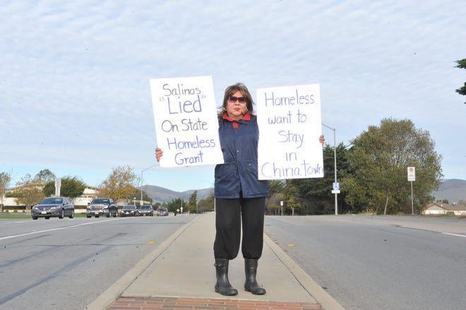 Yolanda Hayes, a Creekbridge resident, holds signs protesting the proposed homeless shelter at 855 E. Laurel Dr. in Salinas