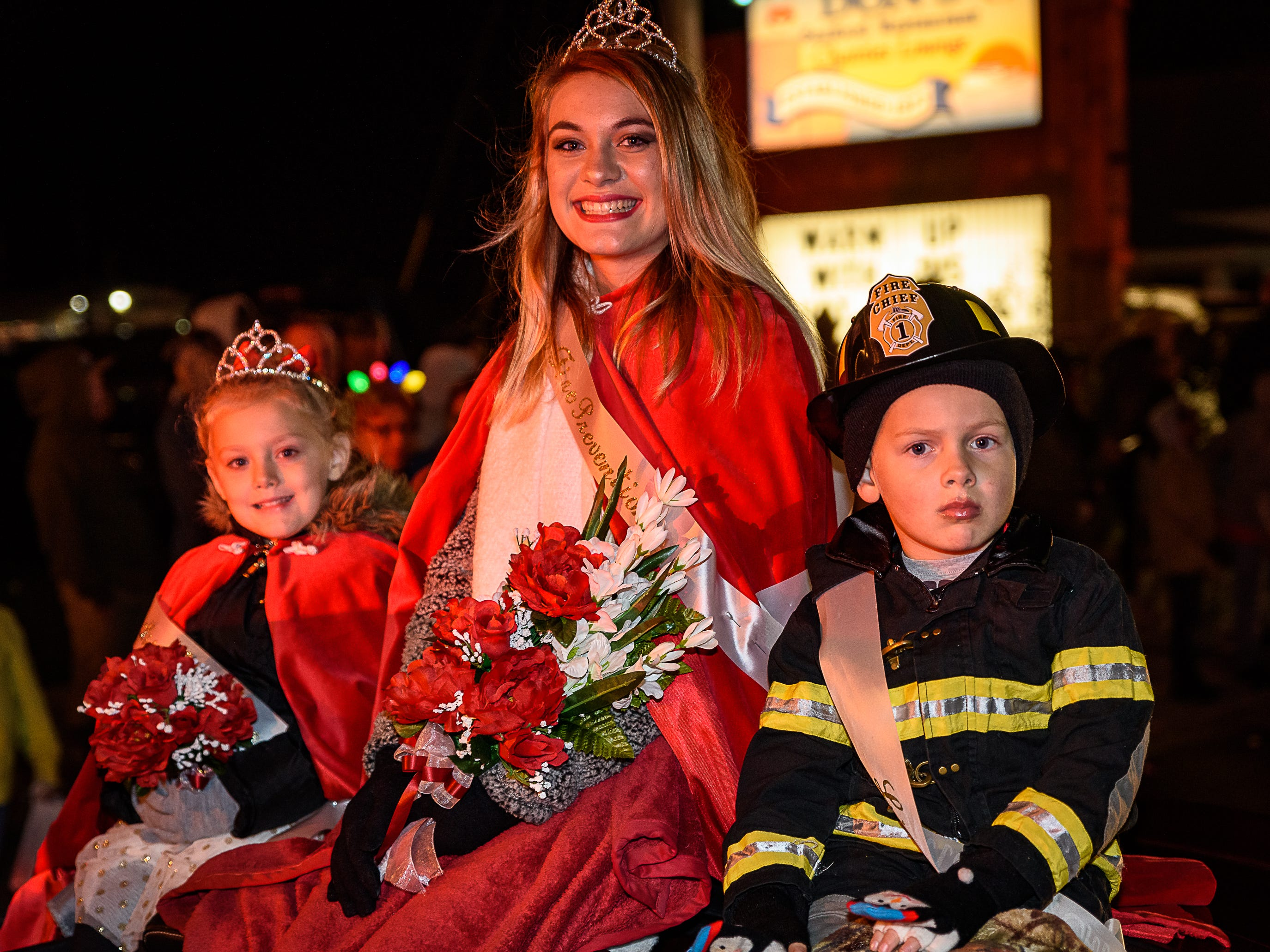Miss Pocomoke Fire Prevention, center, rides in the Chincoteague Christmas parade with Little Miss and Little Mr. Fire Prevention.