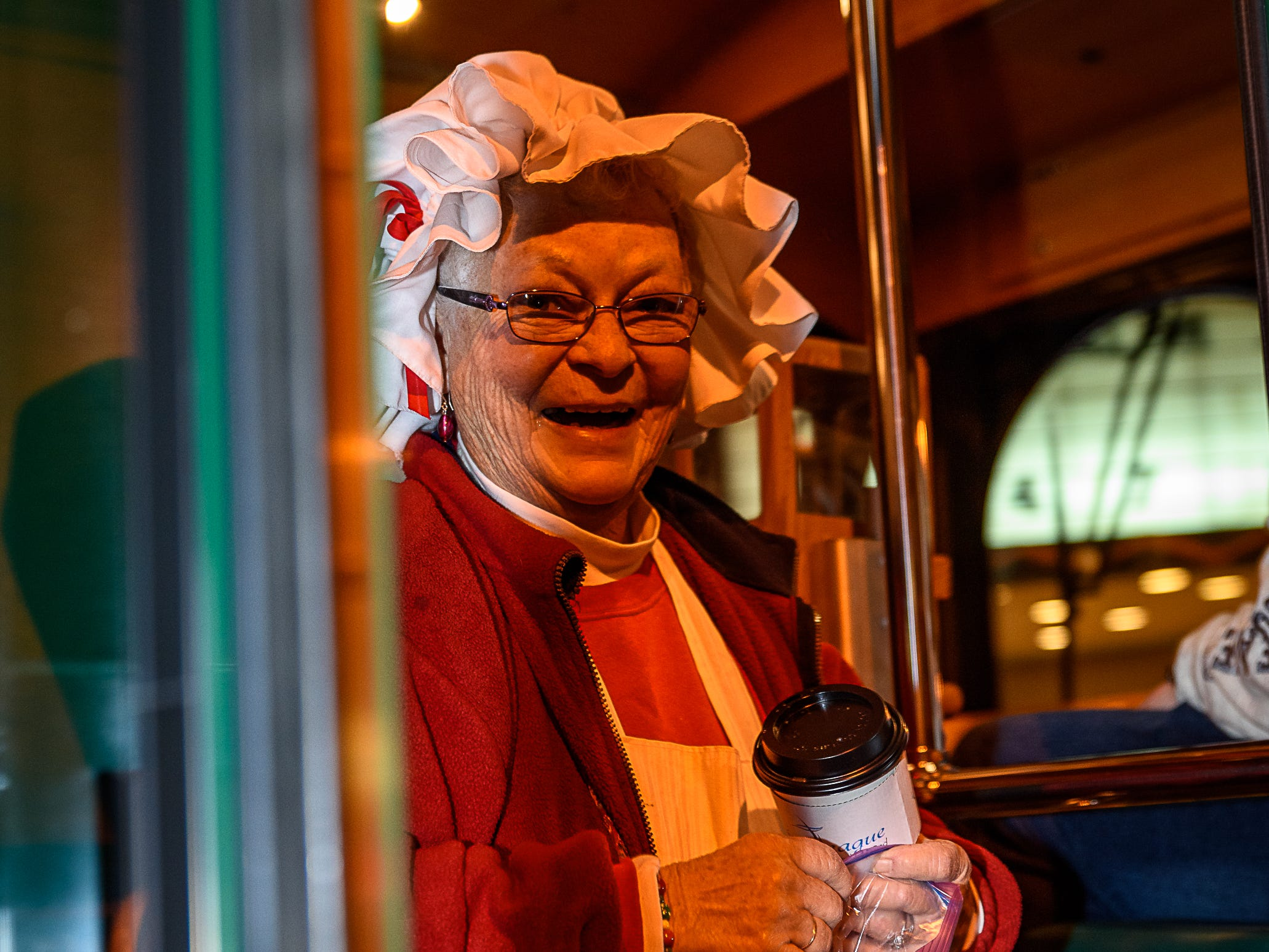 Mrs Claus hands out treats from the door of the Chincoteague Trolley during the Christmas parade.