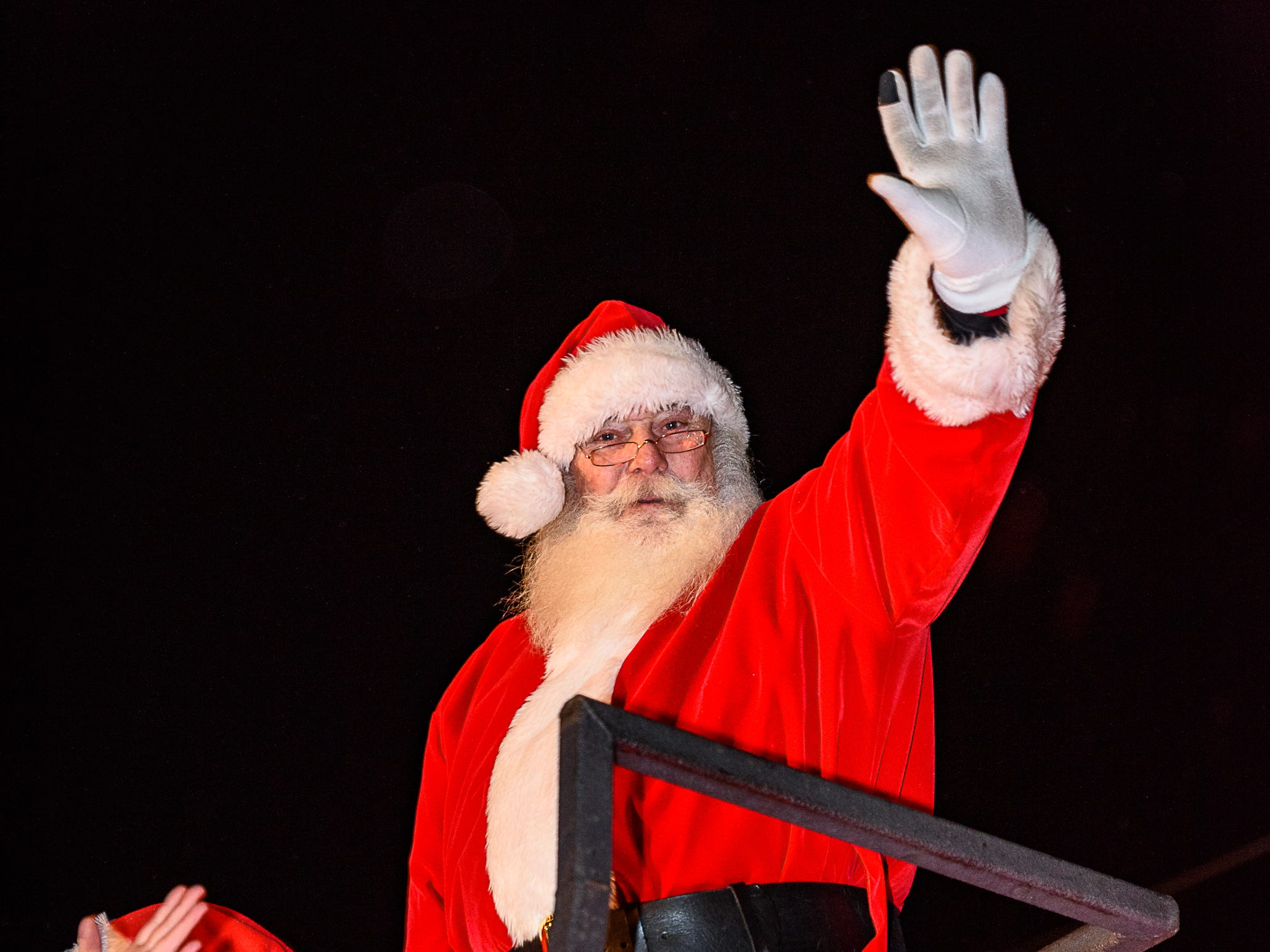 Santa waves to the crowd from atop a Chincoteague fire company ladder truck during the Christmas parade.