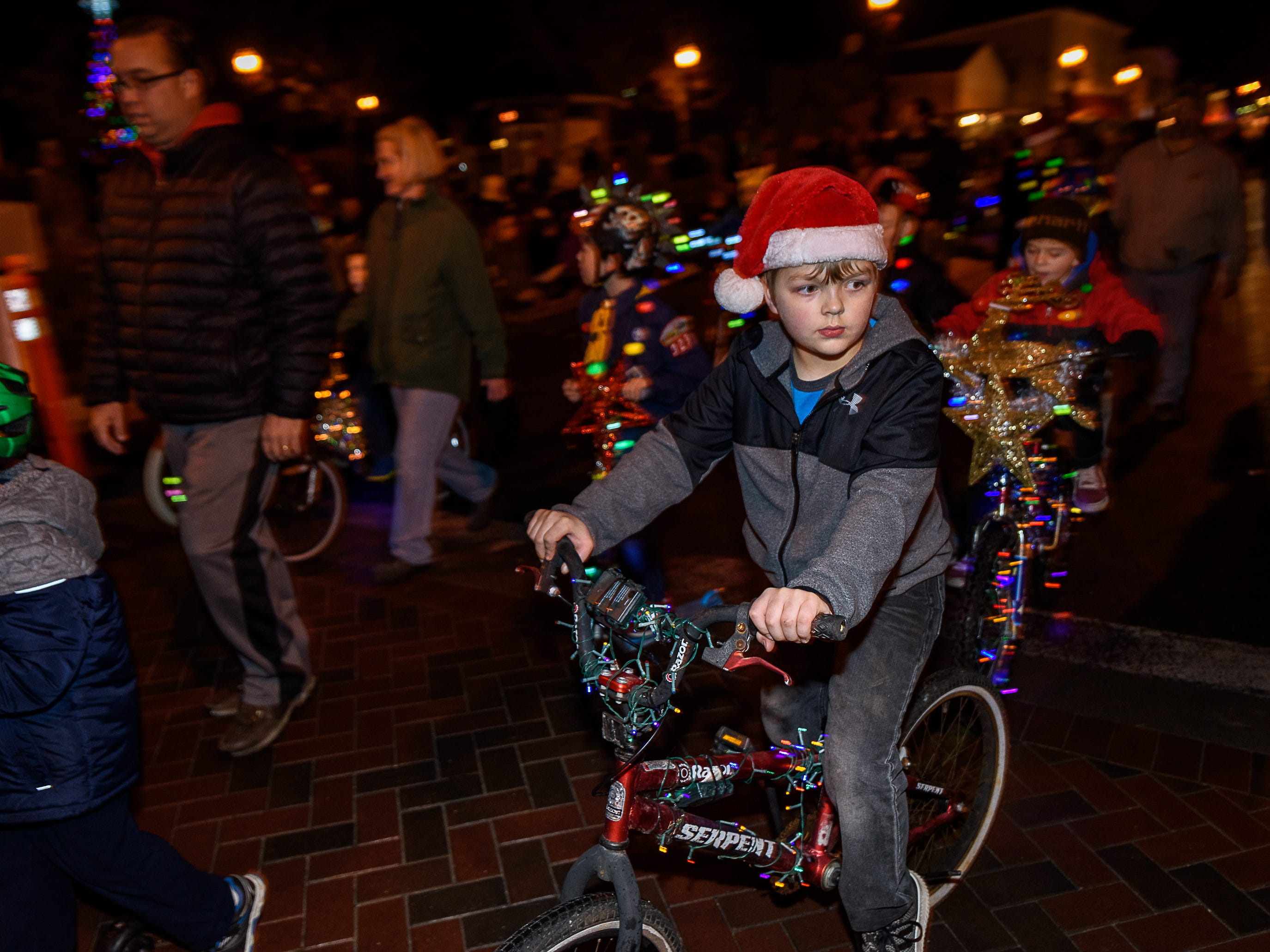 Members of the local Cub Scout Pack ride their decorated bikes in the Chincoteague Christmas parade.
