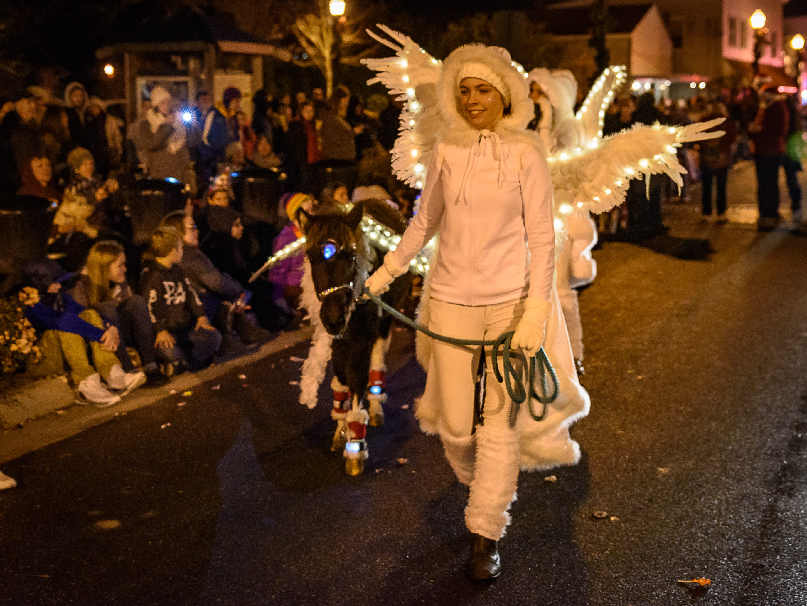 Members of The Angel Squad, a group that cares for orphaned foals, takes part in the Chincoteague Christmas parade.